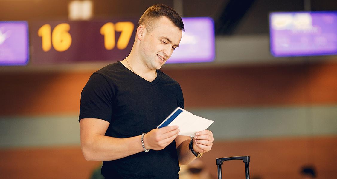 Homem-no-saguão-do-aeroporto-olhando-passagem-aérea