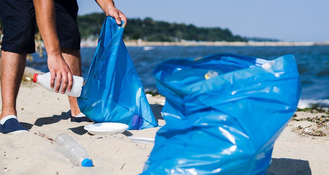Pessoa-coletando-lixo-reciclável-na-praia